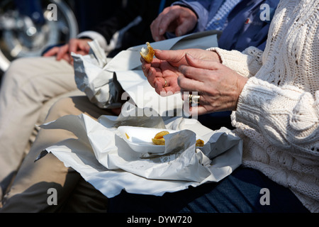 older woman eating fish and chips on a sunny day in the uk - Stock Photo