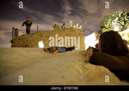 An Israeli soldier stands guard as Ultra-Orthodox Jews pray at the tomb of Nun, the father of the Biblical Israelite - Stock Photo