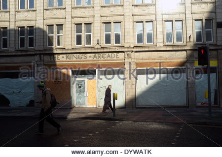 Early morning light reveals a man by empty retail units in The King's Arcade shopping centre, in Doncaster, South - Stock Photo