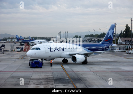 LAN airlines aircraft with tug Comodoro Arturo Merino Benitez International Airport Santiago Chile - Stock Photo