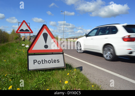lorry passing pothole warning signs on road united kingdom - Stock Photo