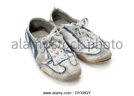 A pair of worn out trainers isolated on white - Stock Photo