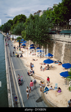 View of the artificial beaches set up by the Paris government during the summer period along the banks of the Seine - Stock Photo