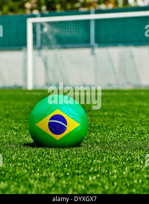 Soccer Ball with Brazilian Flag on the grass in stadium - Stock Photo