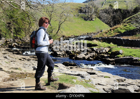 Lady Rambler standing by a river in the Yorkshire Dales - Stock Photo