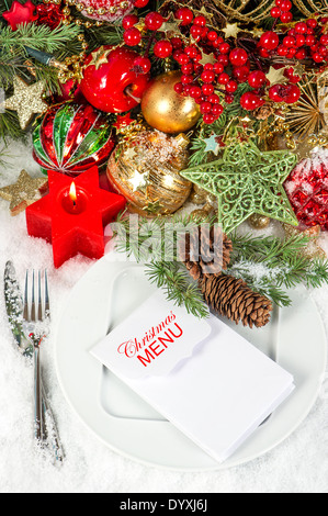 festive christmas table place setting decoration with red candle - Stock Photo