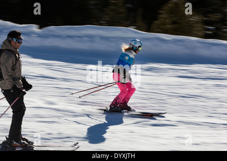 A girl with helmet, goggles and bright pink trousers speeds down the piste. - Stock Photo