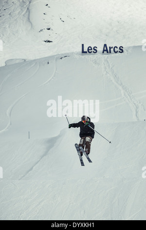 Skier jumps high with Les Arcs sign in the background. - Stock Photo