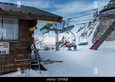 Skiers alight from the Grand Renard chairlift in Les Arcs. - Stock Photo