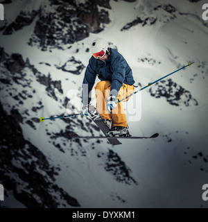 Skier with helmet and goggles jumps high whilst crossing skis. - Stock Photo