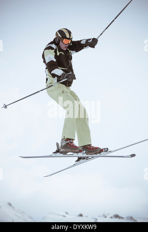 Skier jumps high with mountain peaks in the background. - Stock Photo