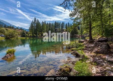 Small alpine lake Laux surrounded by trees in Italian Alps. - Stock Photo