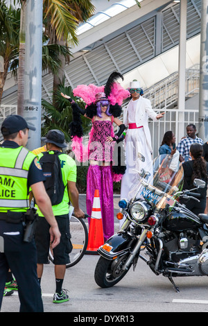 Male and female stilt walkers in colorful costumes at 2014 Mercedes-Benz Corporate Run in Miami, Florida, USA. - Stock Photo