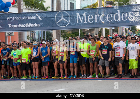 First-place winners Tyler McCandless and Kristen Arendt wait with other runners at start of 2014 Mercedes Benz Corporate - Stock Photo