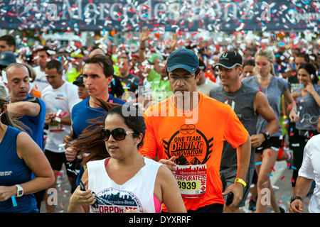 Throng of men and women runners crowd together at start of 2014 Mercedes-Benz Corporate Run in Miami, Florida, USA. - Stock Photo