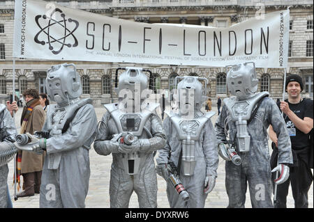 Somerset House, London, UK. 27th April 2014. Multiple Cybermen pose with the banner in Somerset House for the Sci - Stock Photo