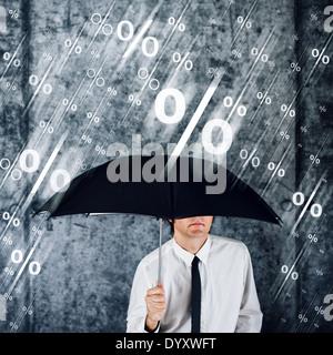 Businessman with umbrella protecting himself from rain of percentage symbols. - Stock Photo