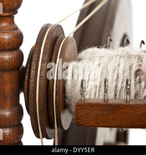 Close-up of wooden handmade spinning wheel against white background - Stock Photo