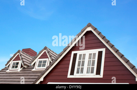 Brown tile roof in garden against blue sky. background - Stock Photo