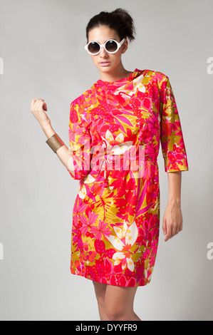 A black hair woman with ponytail, multiracial female model wearing a 60s pink floral dress and round sunglasses - Stock Photo