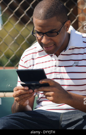A young man, African American playing a handheld video game. He sits on a bench at school fully focused on playing - Stock Photo