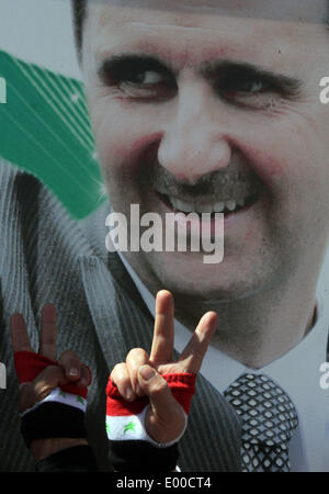 Damascus, Syria. 28th Apr, 2014. Syrians make victory signs with hands during a rally to show support for President - Stock Photo