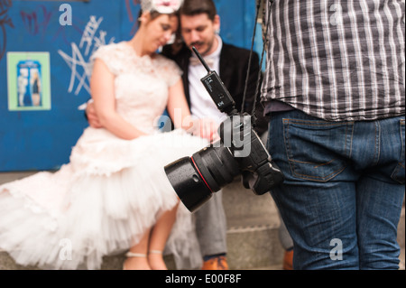 Alternative wedding photographer on a shoot with a couple in vintage clothes looking at the wedding ring in front - Stock Photo