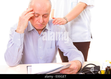 doctor comforting mature stressed patient with headache - Stock Photo