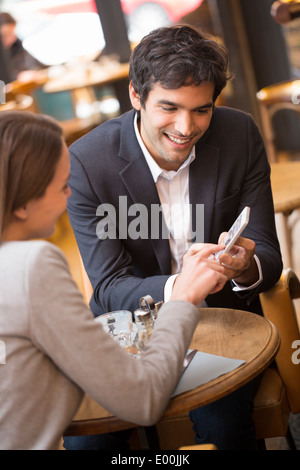 Man woman using cell phone coffee bar - Stock Photo
