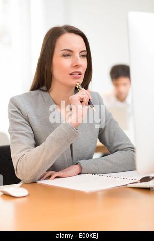 Pretty woman desk computer background colleague - Stock Photo