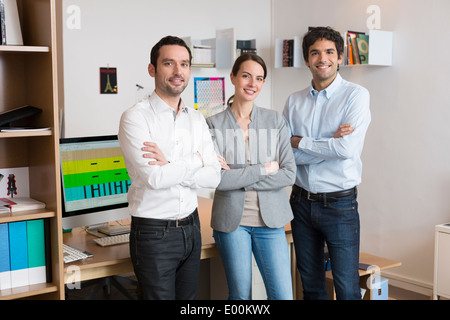 Female male desk colleagues group looking camera - Stock Photo
