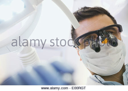 Dentist in dental loupes performing checkup - Stock Photo