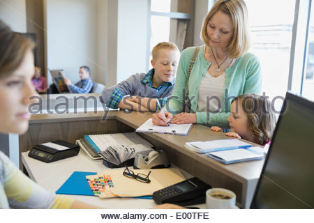 Woman filling out paperwork at dentists office - Stock Photo