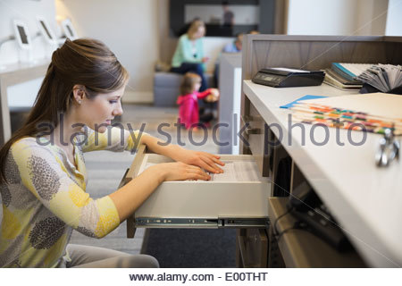 Receptionist looking through drawer in dentists office - Stock Photo