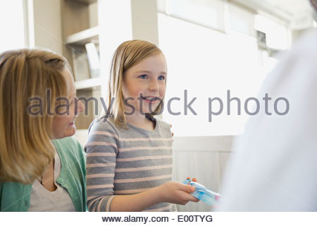 Mother and daughter talking to dentist - Stock Photo