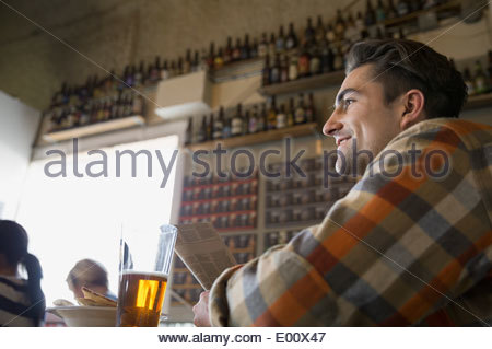 Man reading newspaper and drinking beer at brewery - Stock Photo