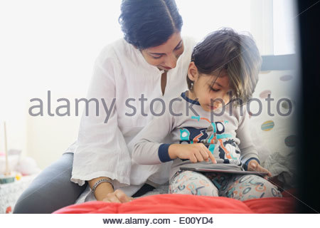 Mother and son using digital tablet on bed - Stock Photo