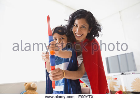 Portrait of mother and son in superhero costumes - Stock Photo