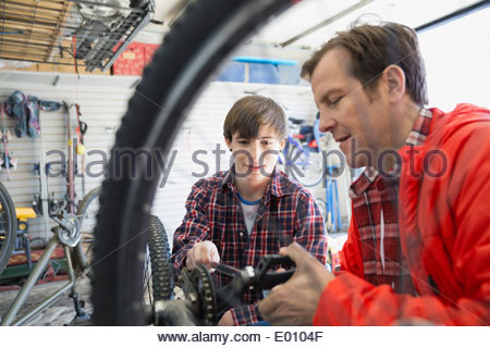 Father and son repairing bicycle in garage - Stock Photo