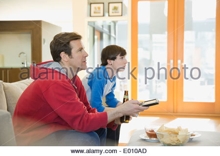 Father and son watching TV in living room - Stock Photo