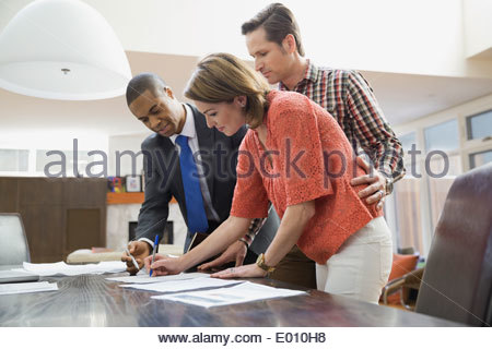 Couple signing documents for financial advisor - Stock Photo