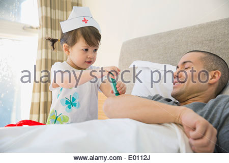 Daughter playing nurse to father in bed - Stock Photo