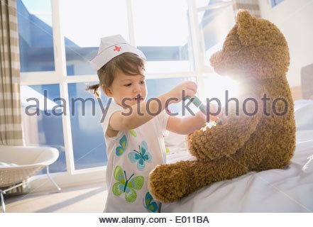 Girl in costume playing nurse to teddy bear - Stock Photo