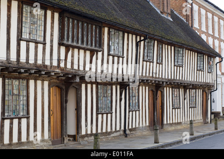 Lady looking out of a window from the15th century black and white half timbered almshouses in Church Street, Stratford - Stock Photo