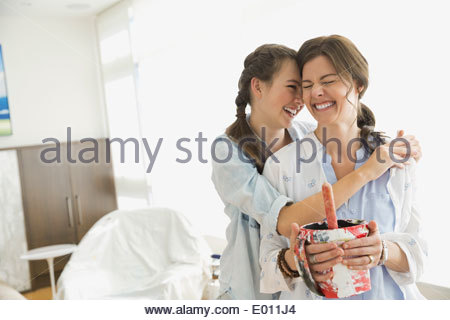 Affectionate mother and daughter preparing to paint - Stock Photo