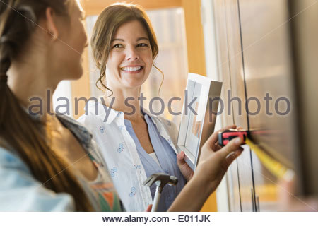 Mother and daughter measuring wall - Stock Photo