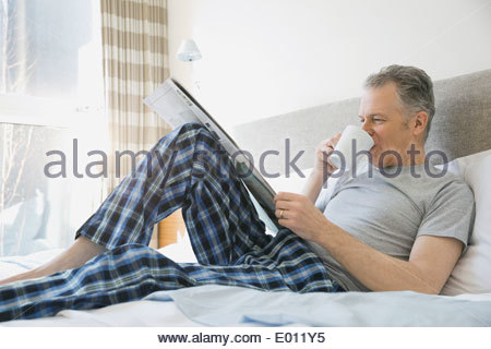 Man drinking coffee and using newspaper on bed - Stock Photo