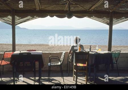 Woman at a beach bar on Naxos Island, 1972 - Stock Photo