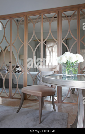 Mirror patterned wardrobe doors in guest bedroom of St Tropez villa with circular table with white roses in foreground - Stock Photo