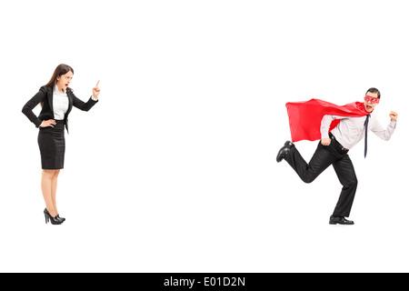 Superhero running away from an angry businesswoman - Stock Photo